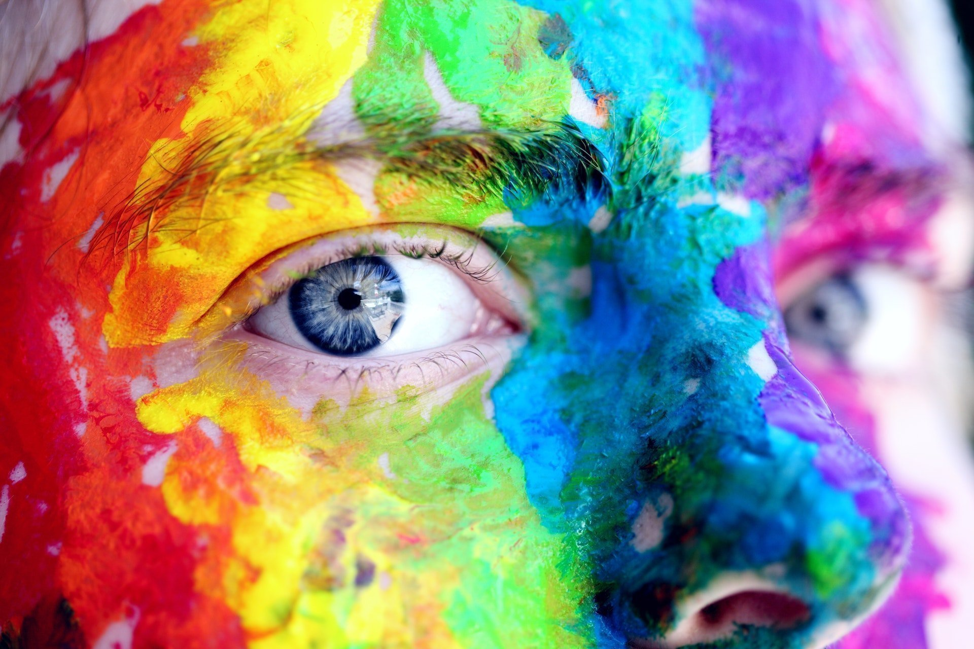 colorful paint applied to a person's face. The close up shows the influence of color psychology in their eyes