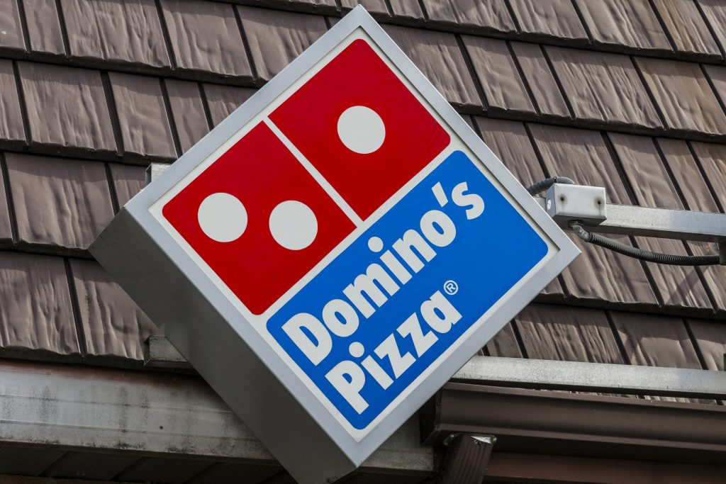 Domino's pizza logo box on the roof of a Domino's pizza parlor